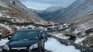 Cars abandoned overnight on a snow-covered pass in the Lake District.