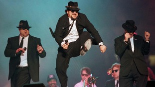 John Belushi jumps as the Blues Brothers perform at the half time show at Super Bowl in 1996.