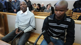 Chris Mahlangu, (L) and Patrick Ndlovu, (R), sit inside the court in Ventersdorp, South Africa,