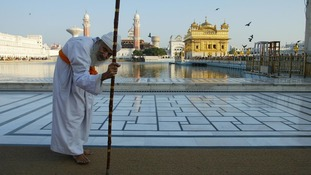 A pilgrim slowly makes his way to the Golden Temple of Amritsar.