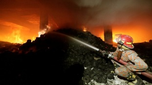 A firefighter tries to control a fire at a garment factory in Savar, outskirts of Dhaka.