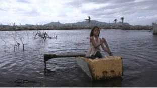 Rose, 9, uses an upturned refrigerator as a small paddle boat