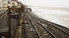 A huge length of railway track is exposed and left hanging after the sea wall collapsed in Dawlish.