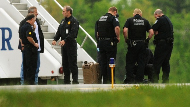 Law enforcement officials stand near a jet bridge next to the passenger jet on the tarmac