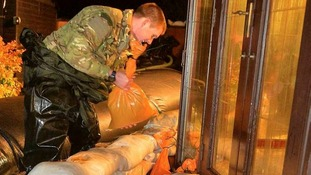 A Marine builds a flood defence around a building in Moorland