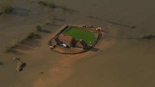 The house is surrounded by flooded fields.