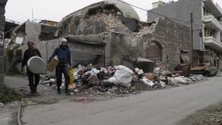 Residents walk by a damaged old house in the besieged area of Homs