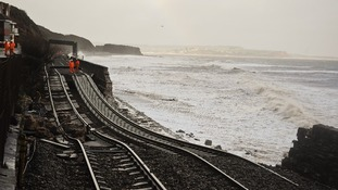 A huge length of railway track is exposed and left hanging after the sea wall collapsed in Dawlish