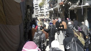 Civilians carry their belongings as they wait to be evacuated from Homs