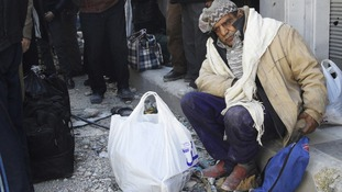 A civilian sits with his belongings as he waits to be evacuated from a besieged area of Homs