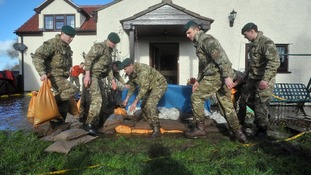 Royal Marines from 40 Commando help to place sandbags to protect a property in Moorland, Somerset.