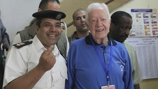 Former U.S. President Jimmy Carter, poses with an Egyptian policeman inside a polling station in the Sayeda Aisha neighborhood of Cairo