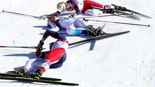 Competitors in the women's skiathlon collapse into a heap after their event