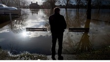 A resident looks out across the river Thames that has flooded Datchet in Berkshire