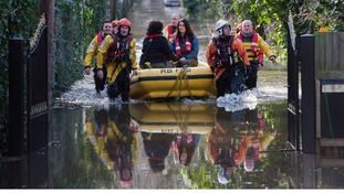 Members of the Royal Berkshire Fire Service rescue residents whose houses have been flooded in Staines-upon-Thames