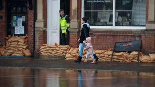 Residents walks through the village centre following flooding in Datchet, Berkshire