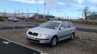 Silver Skoda car parked.