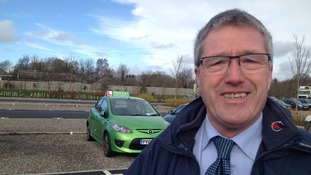 Allan stands in front of his green Mazda car