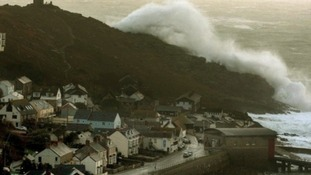 A wave breaks over a headland in Sennen Cove near Land's End