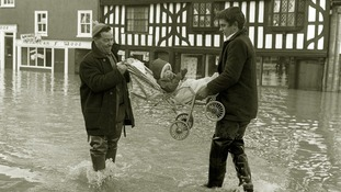 Caroline Abell, a seventeen month old baby is carried through the swirling flood waters at Frankwell, Shrewsbury, Shropshire.