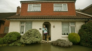 Nikki Vipers from Egham, Surrey looks at the flooded garden of her parent's home in Egham, Surrey.
