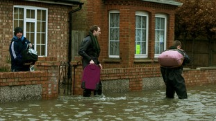 Members of the army carry belongings to higher ground in Egham, Surrey.