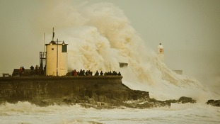 Waves break over Porthcawl harbour, south Wales, as the region continues to be battered high winds and heavy rain.