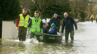 Residents pull a boat through flooding in Wraysbury, Berkshire.