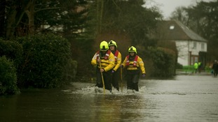 Firefighters wade through flooding in Wraysbury, Berkshire.