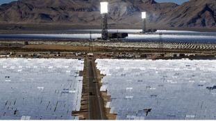 Heliostats reflect the sunlight onto boilers in towers  at the opening of the Ivanpah Solar Electric Generating System.