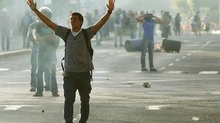 Anti-government demonstrators walk through tear gas in the Venezuelan capital Caracas.
