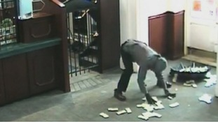 The suspect frantically tries to put all the money into an open umbrella.
