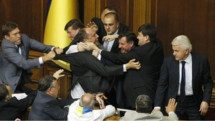 Speaker of the Ukrainian parliament Volodymyr Lytvyn looks on as deputies scuffle