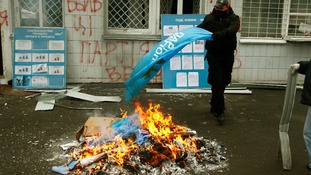 An anti-Yanukovich protester burns flags of the Party of Regions in Kiev.