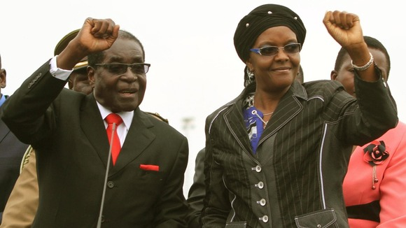 Zimbabwean President Robert Mugabe and his wife Grace wave to the crowd.