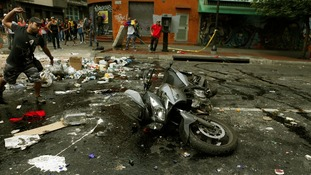 Protester throws stones at a motorcycle after the rider tried to pass a barrier.