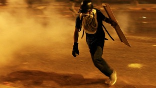 Anti-government demonstrators run from tear gas during clashes in Caracas.