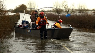 A man pull a boat in Somerset during the flooding that engulfed thousands of homes in January and February.