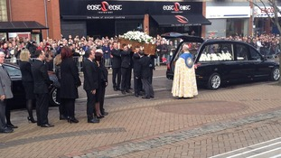 Players past and present carry the coffin as thousands watch on to say goodbye