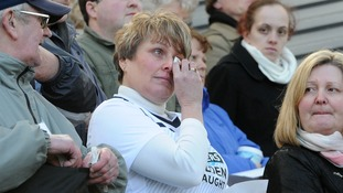 A woman in a Preston North End shirt appears tearful as the service is shown