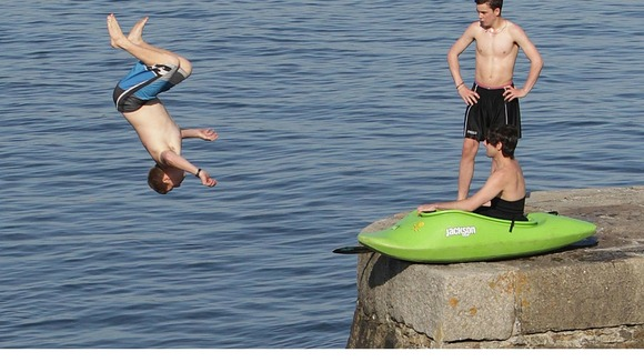Young men jump into the water off a sea wall at Bray, Co. Dublin as the warm weather continues across Ireland