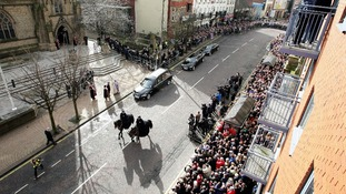 Crowds are shown packed in around Preston Minster as Sir Tom's funeral cortege arrives
