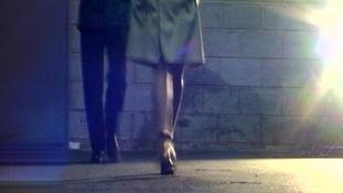 A women walks with a man behi