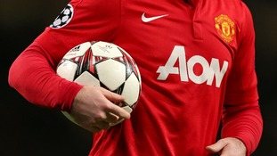 Manchester United's Wayne Rooney holds an official UEFA Champions League match ball.