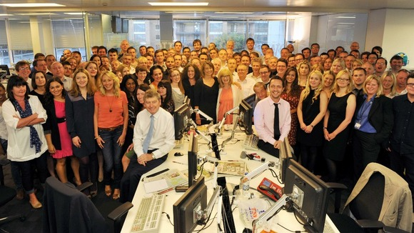 The News Of The World editor, Colin Myler (FRONT L), poses with the staff of the newspaper the day before its planned closure
