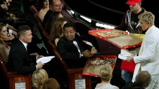 Brad Pitt and 12 Years a Slave's Chiwetel Ejiofor take some pizza during the Oscars ceremony.