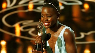 Lupita Nyong'o smiles as she receives her Best Supporting Actress Oscar for 12 Years a Slave.