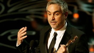 Gravity director Alfonso Cuaron accepts his Oscar.