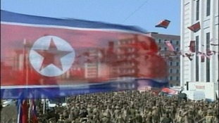 A North Korean flag is seen above the amassed crowds
