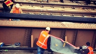 Two men lift metal from a rail track after the explosion.